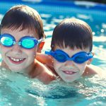 Happy little kids in goggles smile in pool
