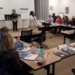Attendees at tables provide input to facilitators who record the items on flip charts at the Comprehensive Opioid Abuse (CARA) Planning Grant Regional Mini-Cross Systems Mapping event.