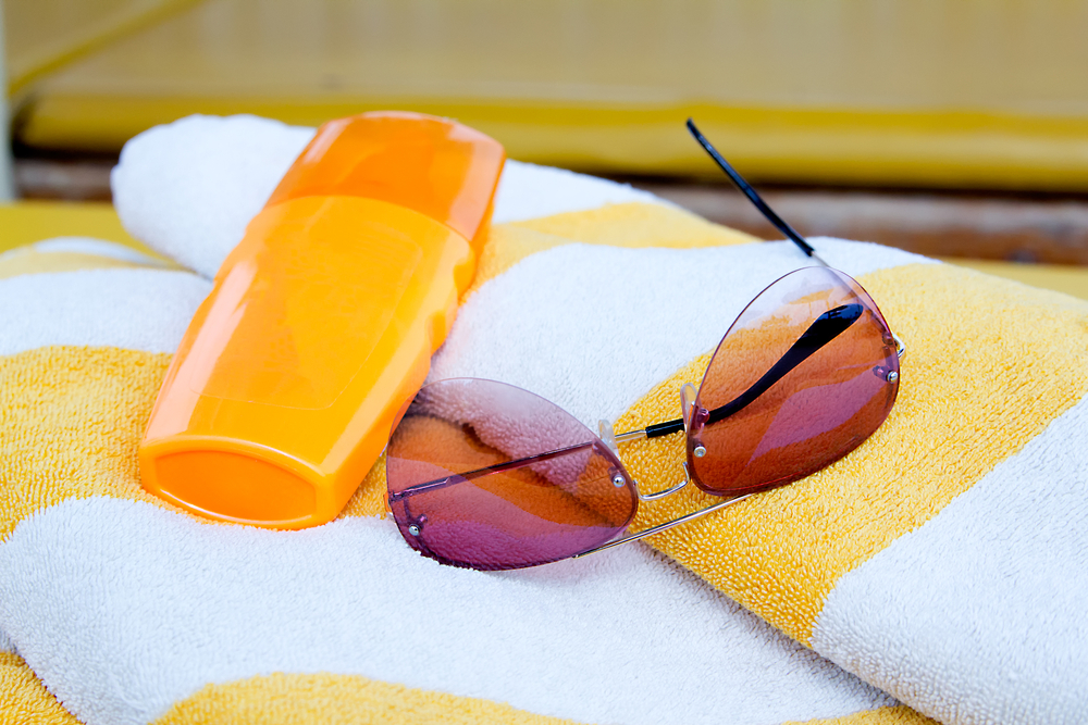 A yellow and white striped towel with sunglasses and sunscreen.