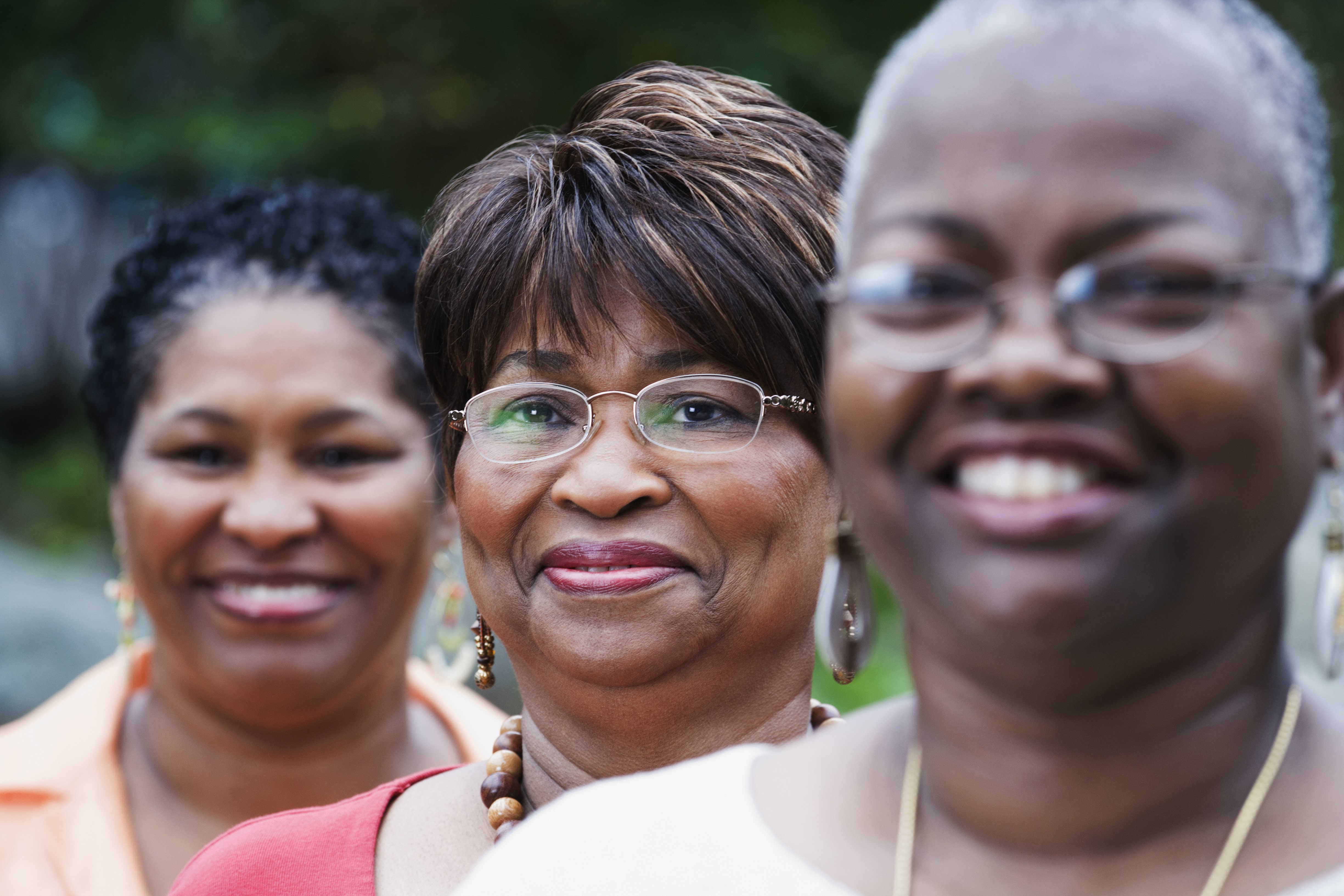 Three older african-american women standing outdoors smiling