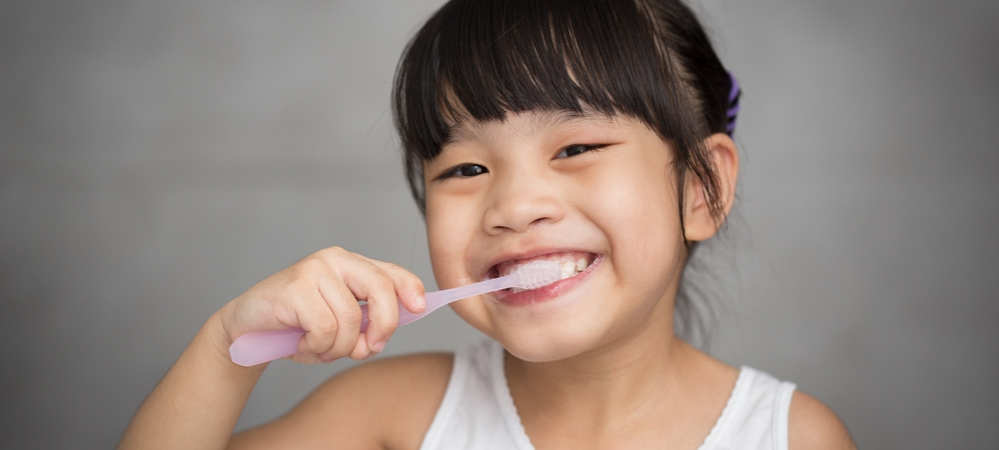Little girl brushing her teeth with a light pink toothbrush.