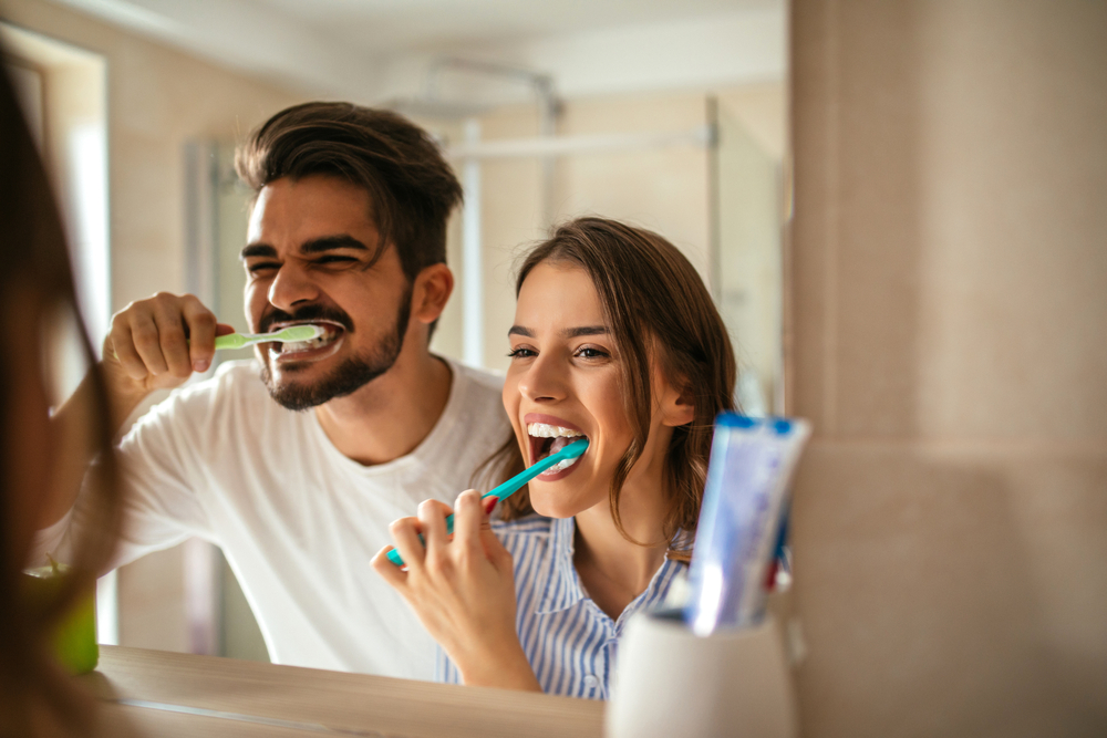 A man and woman looking in the mirror and brushing their teeth