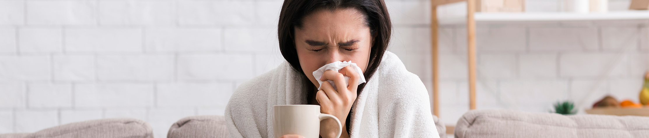 a woman who is sick sitting on her couch with a blanket around her shoulders holding a ceramic mug and sneezing into a tissue.
