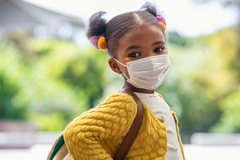 Young girl ready to go to school with face mask