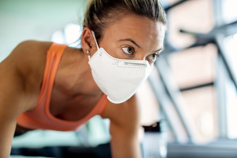 Close-up of sportswoman with protective face mask exercising at health club.