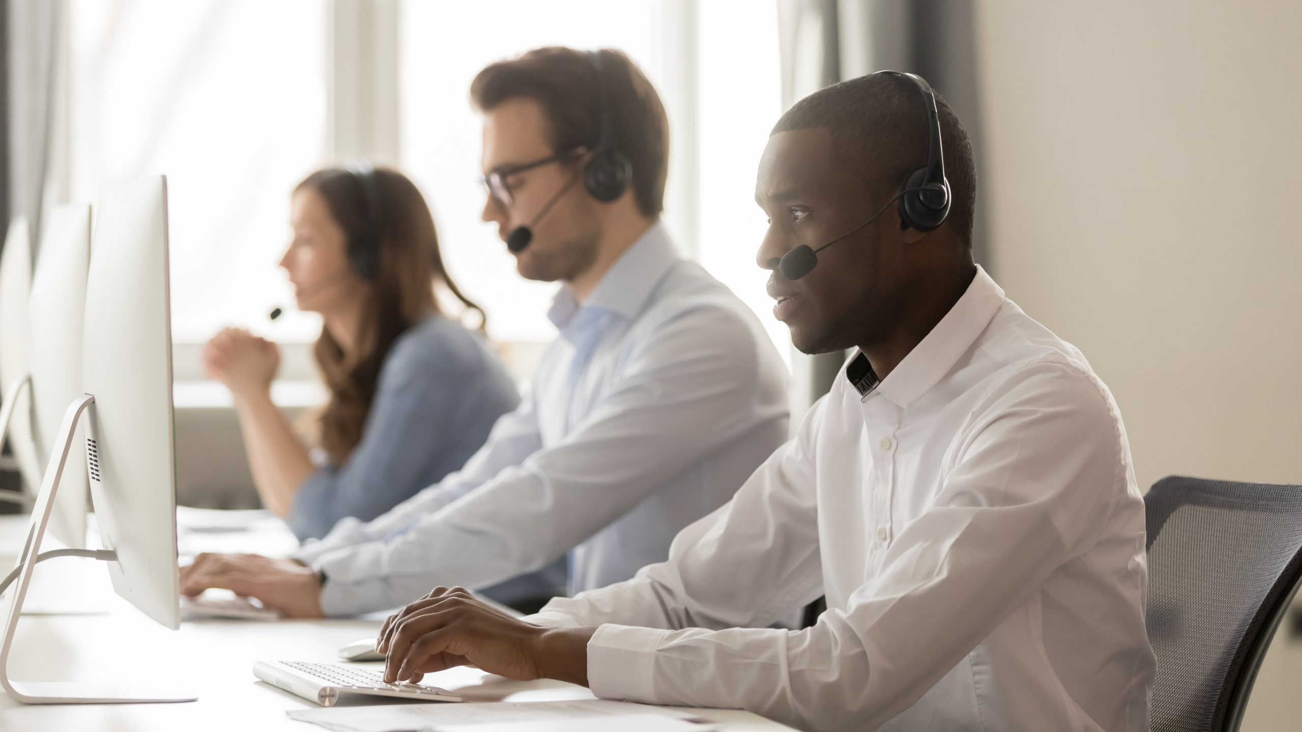 call center agent in wireless headset working on computer with diverse team, focused black male operator telemarketer using pc in customer support service group office, help desk.