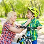 mother taking care of her son, wearing his bicycle helmet
